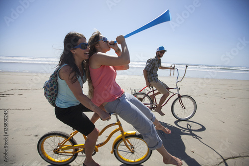Photo  Two women and one man riding bikes, having fun on the beach in San Diego, California