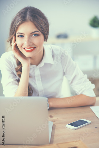 Fototapety, obrazy: Attractive businesswoman sitting on a desk with laptop in the office