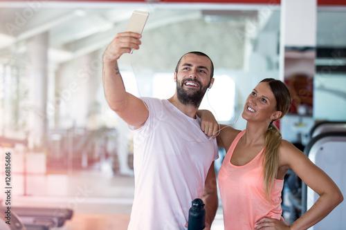 Fototapeta Young couple taking a sefie in a gym obraz na płótnie