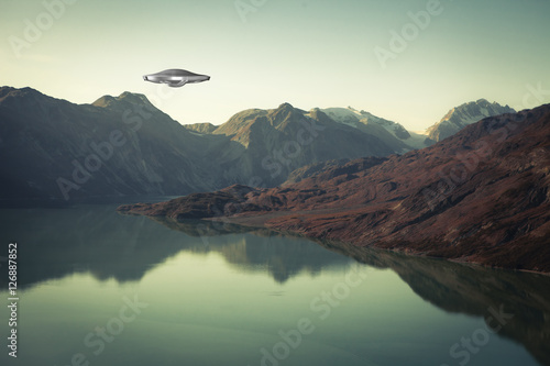 Foto op Canvas UFO UFO Spaceship with water and mountains.