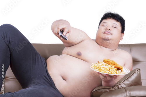 Fotografering  Fat man watch tv on sofa