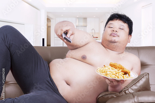 Obesity person watches tv at home Canvas Print