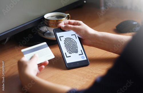 Smartphone with fingerprint reader in one hand and credit
