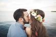 Wedding couple sitting on large stone around blue sea
