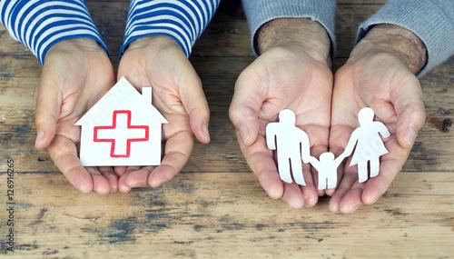 Hände halten Papierfamilie und Papierhaus mit roten Kreuz Wallpaper Mural
