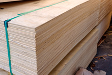 Sheets Of Stacked Plywood In Lumberyard. Shallow Focus And Blurred Background. Copy Space.