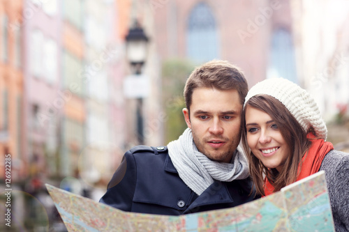 Foto  Pretty couple sightseeing with map