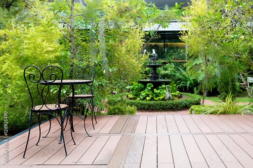 Papiers peints Jardin Black chair in wood patio at green garden with fountain in house