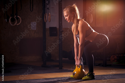 Fotografie, Obraz  Attractive blonde girl exercising with kettlebell