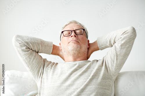 Deurstickers Ontspanning senior man in glasses relaxing on sofa