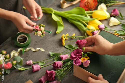 Fotografie, Obraz  Female hands making beautiful flower composition in floral shop