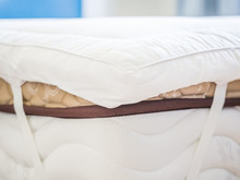 Closeup Of White Topper On The Bed In The Bedroom