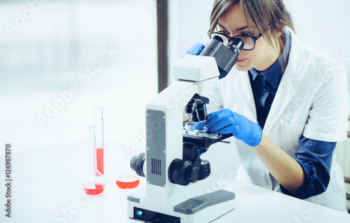 Fotografia Young female doctor looking through a microscope in a laboratory