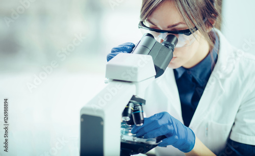 Fotografia  Young scientist looking through a microscope in a laboratory