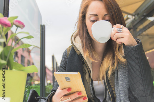 Fotografie, Obraz  Attractive girl using smartphone at restaurant drinking coffe