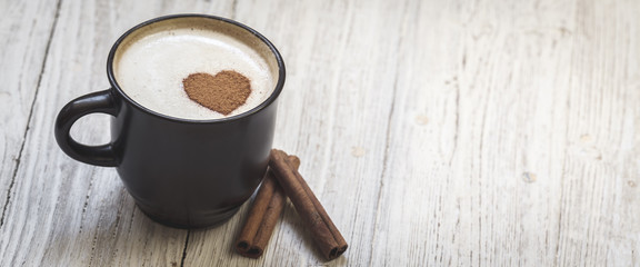 Coffee with cinnamon sticks and heart shape