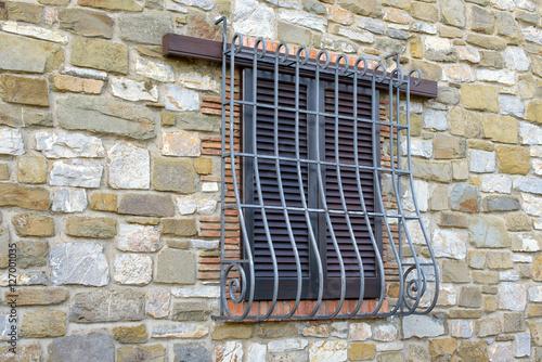 Valokuvatapetti window with iron grating on stone wall