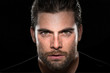 Handsome male model with masculine facial hair and intense eyes on isolated black background