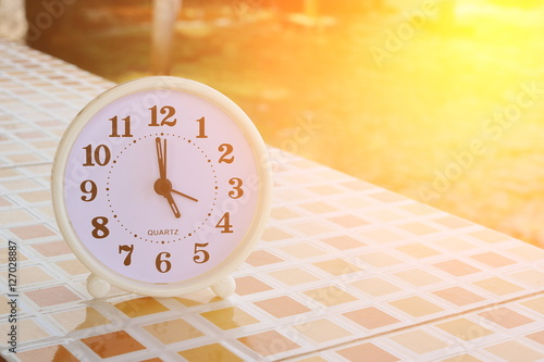 White clock at 5 pm on the tiled floor and seashore background , Freedom concept Canvas Print