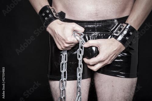 Photo  dominanter mann in latex shorts mit stahl kette