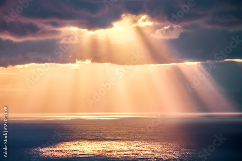 Rays of light after rain storm, seascape with sun reflections on water surface Canvas Print