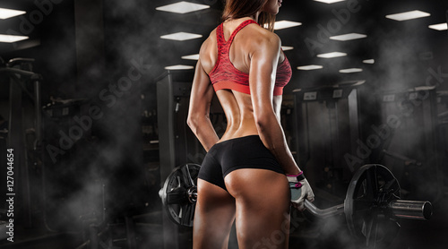 Photo sur Toile Fitness Nice sexy woman doing workout with dumbbells in gym