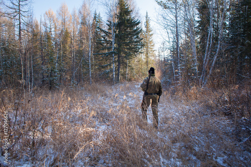 Foto op Aluminium Jacht a hunter in the winter woods with a gun in camouflage clothing.