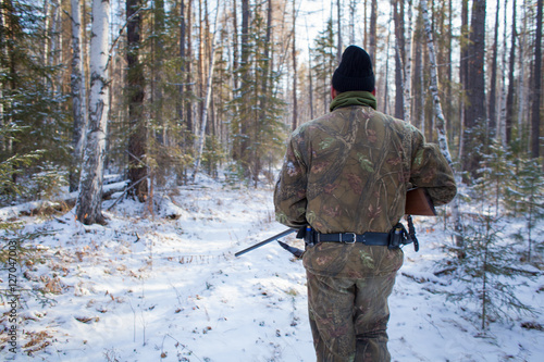 Fotobehang Jacht a hunter in the winter woods with a gun in camouflage clothing.