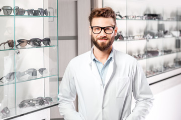 Portrait of a handsome ophthalmologist in front of the showcase with eyeglasses in the hospital