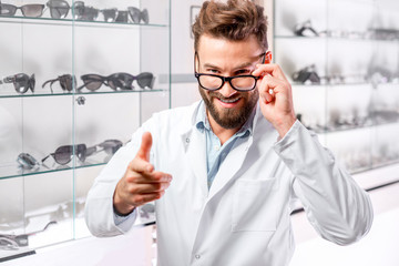 Portrait of a handsome ophthalmologist wearing eyeglasses in front of the showcase with eyeglasses in the hospital