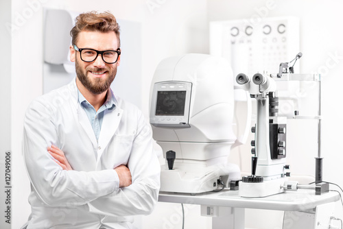 Fotografía  Portrait of handsome eye doctor sitting with ophthalmologic device in the cabine