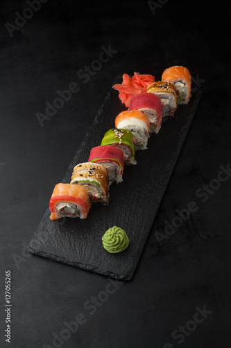 Sushi Roll with avocado, salmon, tobiko, tuna and eel on a black Wallpaper Mural