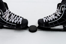 Men's Hockey Skates And The Puck On A Snowy Background