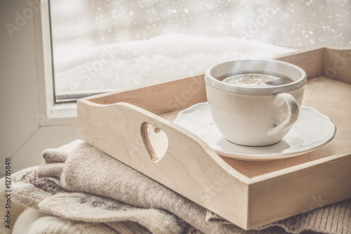 Photo sur Toile The Tea on tray and sweater in from of snowing winter