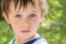Little Boy With Beautiful Blue Eyes Looking Sad, Frustrated