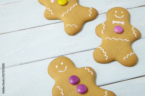 Hand Decorated Gingerbread Men On A Painted Wooden Table Background