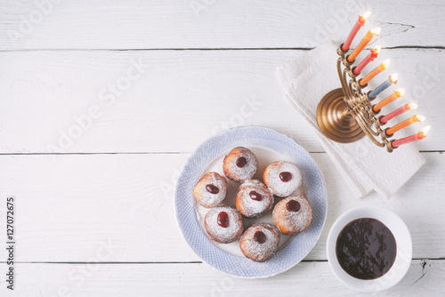 Hanukkah menorah and sufganiot on the white  wooden table top view Canvas Print