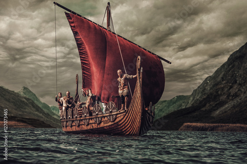 Fotografía  Group of vikings are floating on the sea on Drakkar with mountains on the backgr