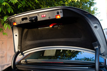 Open The Tailgate Of A Luxury Sedan Car With The Control Buttons And Signal Lights