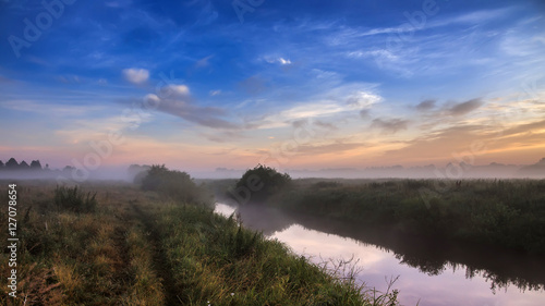 Wall Murals Cappuccino wonderful dramatic scene. fantastic foggy sunrise over the meadow with colorful clouds on the sky. picturesque rural landscape, misty morning. color in nature. beauty in the world