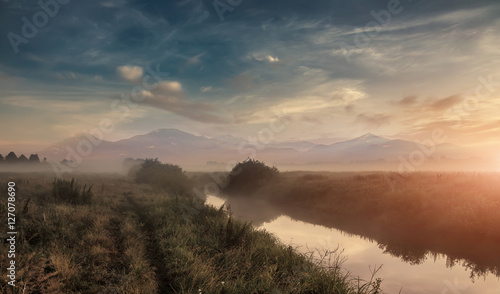 Wall Murals Cappuccino misty morning over the meadow. foggy sunrise on the river. majestic mountaines on the background, blurry. creative image
