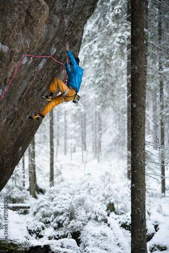 Fotobehang Wintersporten Outdoor winter sport. Rock climber ascending a challenging cliff. Extreme sport climbing.