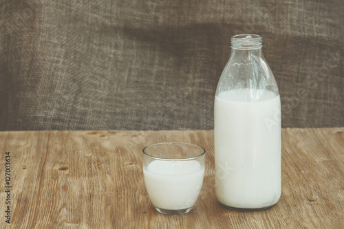Fotobehang Zuivelproducten Bottle of fresh milk and one glass on wooden table