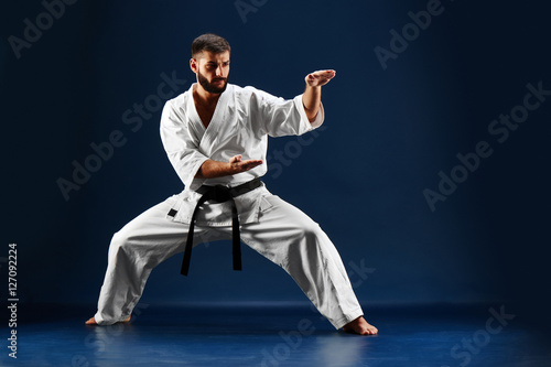 Carta da parati Karate man in a kimono standing in a fighting stance on a blue background