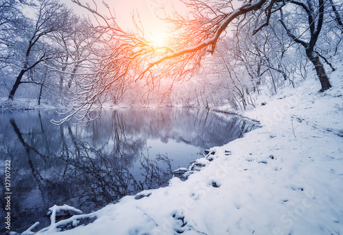 Papiers peints Rivière de la forêt Winter forest on the river at sunset. Colorful landscape with snowy trees, frozen river with reflection in water. Seasonal. Winter trees, lake, sun and blue sky. Beautiful snowy winter in countryside