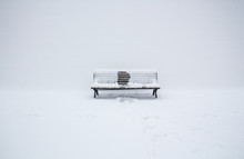 Snow-covered Wooden Bench With An Imprint Of Someone, Who Had Been Sitting In The Middle; Winter Has Gone