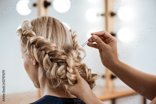 Recess Fitting Hair Salon Female hairdresser making hairstyle to blonde girl in beauty salon.