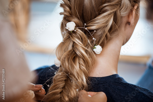 Foto auf Gartenposter Friseur Female hairdresser making hairstyle to blonde girl in beauty salon.