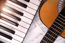 Piano And Guitar With Shine And Sheet Music Background Top