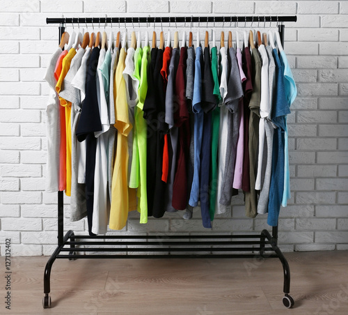 Colorful t-shirts on hangers against brick wall - Buy this